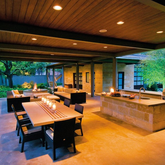 Outdoor kitchen and living area with poured concrete columns, floor, countertops, and fireplace surround; cedar roof supported by iron beams; and natural stone elements, including a custom fire pit.