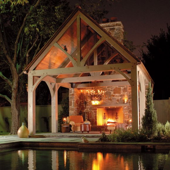 This stone and cedar pavilion, designed to harmonize with the historic Tudor house, features a large, built-in fireplace and wrought iron chandelier.