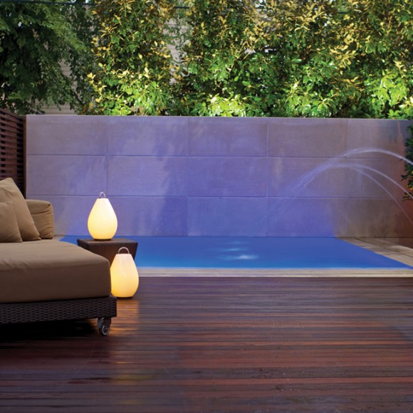 Perimeter-overflow pool with laminar jets, limestone wall and pool coping, Ipe wall and decking, and alternating LED lighting.