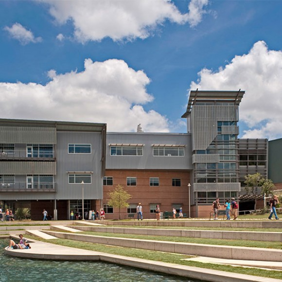 """The signature Live Oak Hall Academic Center on Northwest Vista College's campus contributes to the formation of the new campus """"green"""" on the east side of a lake that bisects the campus. As part of the Alamo Colleges, this new three-story, 86,300-square-foot building houses science laboratories, an astronomy deck, computer labs, classrooms and faculty offices. Perforated screens and awnings control solar heat gain, while allowing views out from the interior spaces. Northwest Vista College - Live Oak Hall"""