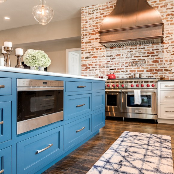 Award-winning kitchen remodel by KBB with oversized copper vent hood and custom blue kitchen island.